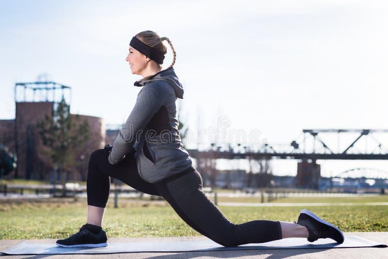 Молодая женщина протягивая ее quadriceps muscles путем хватать ее лодыжку стоковые изображения rf