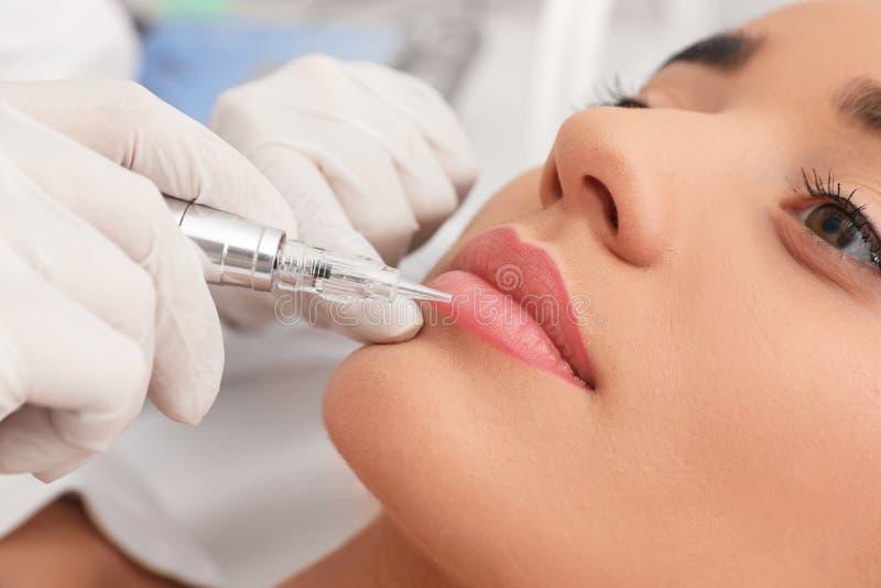 Молодая женщина проходя процедуру постоянной губы стоковая фотография rf