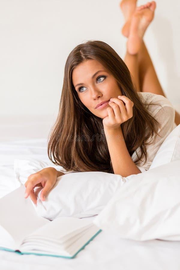 Молодая женщина прочитала книгу в кровати стоковая фотография rf