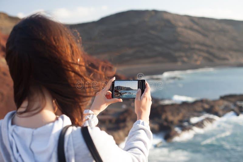 Молодая женщина путешественника принимая фото сценарного пляжа океана с ей стоковое изображение rf