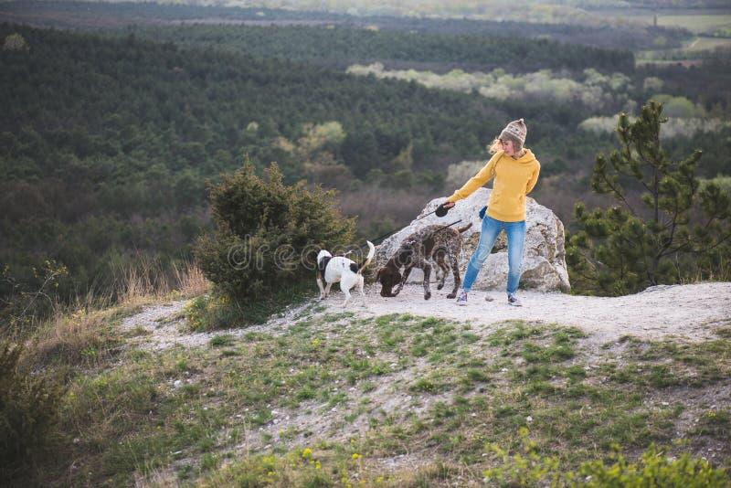 Молодая женщина путешествуя с ее собаками стоковое изображение