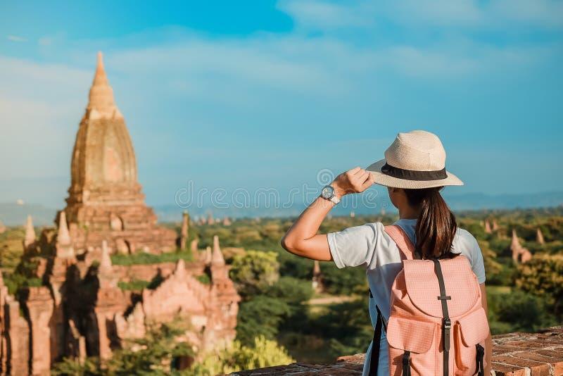 Молодая женщина путешествуя backpacker со шляпой, азиатским положением путешественника на пагоде и выглядя красивыми древними хра стоковое фото rf