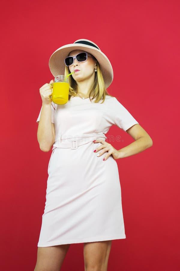 Молодая женщина пьет стакан сока в студии стоковое изображение