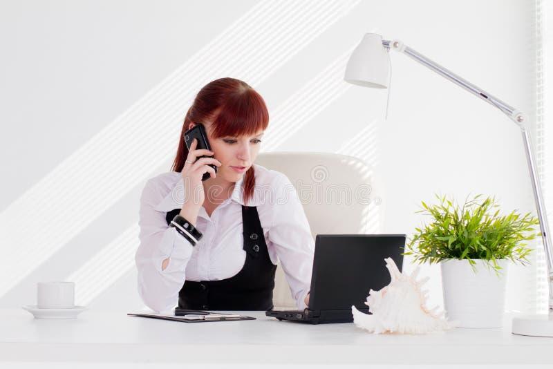 Молодая женщина работая в офисе стоковое изображение