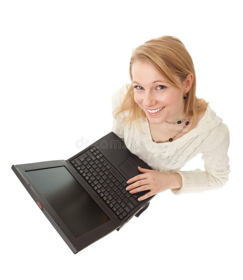 Молодая женщина работая на компьтер-книжке стоковое фото