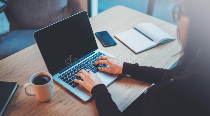 Молодая женщина работая на современной просторной квартире офиса запачканная предпосылка горизонтальный крупный план стоковые изображения rf