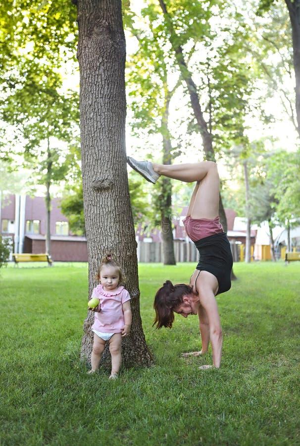 Молодая женщина работая с ее младенцем в парке стоковая фотография rf