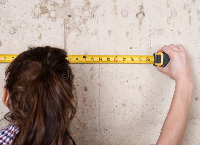 Молодая женщина работая с измеряя лентой стоковые изображения