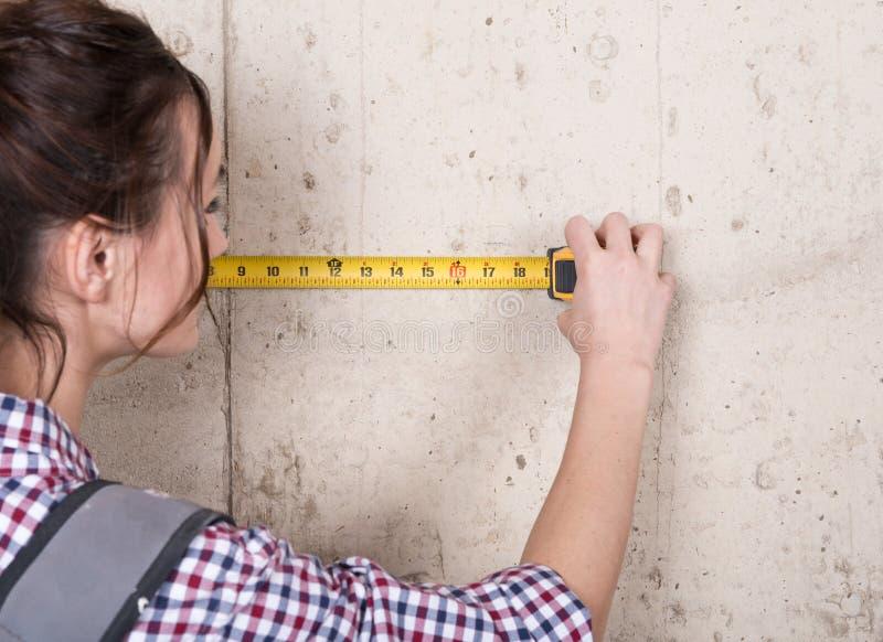 Молодая женщина работая с измеряя лентой стоковое изображение rf