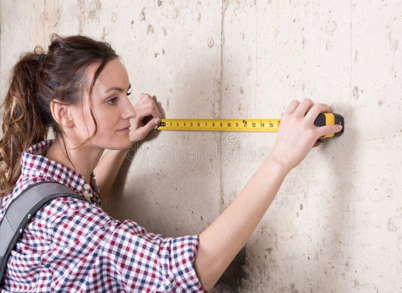 Молодая женщина работая с измеряя лентой стоковые фотографии rf