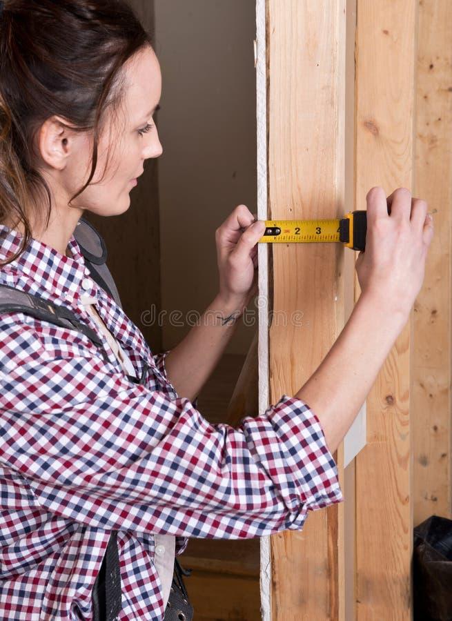 Молодая женщина работая с измеряя лентой стоковая фотография