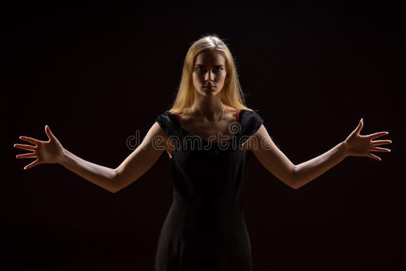 Молодая женщина развевая ее руки Белокурая девушка выражая с поднятыми руками их эмоции в студии на черной предпосылке стоковые фотографии rf