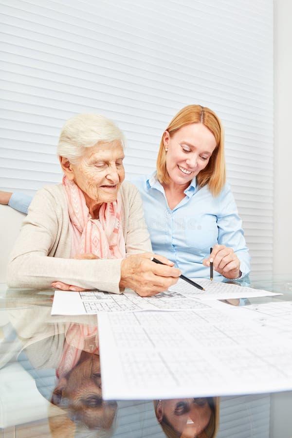 Молодая женщина разрешает головоломки вместе с пожилой женщиной стоковое фото rf