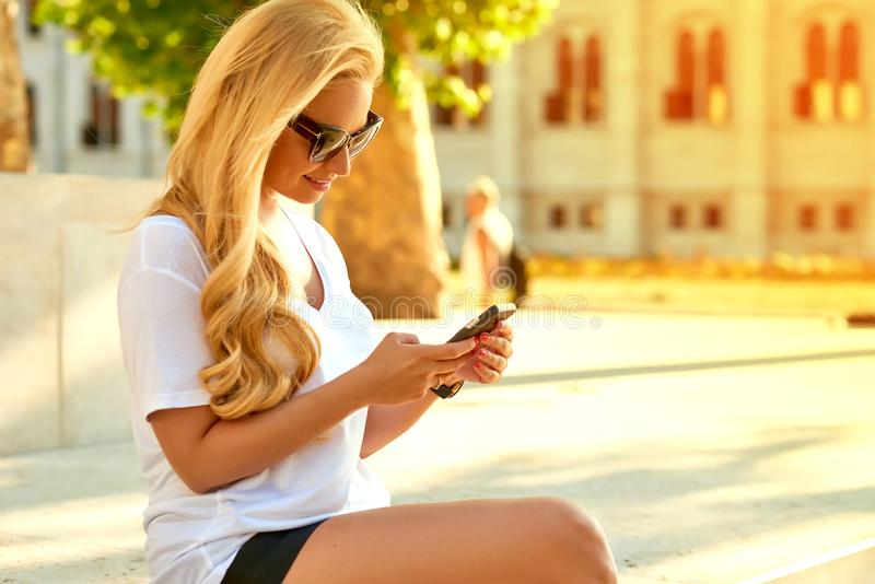 Молодая женщина распологая и используя ее телефон стоковые изображения