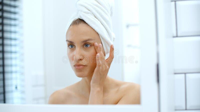 Молодая женщина рассматривая перед зеркалом стоковое фото rf