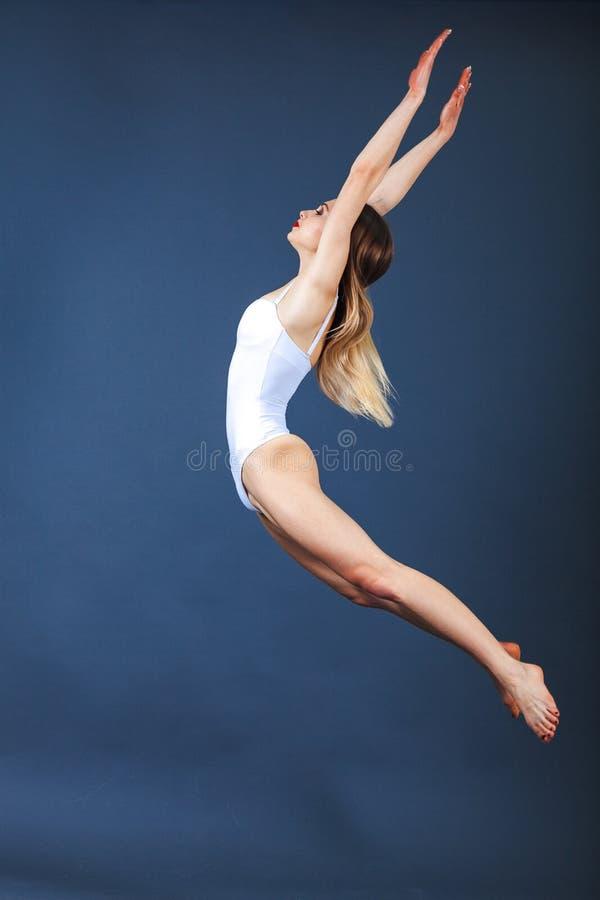 Молодая женщина резвится экстерьер скача вверх по вытягивать руки и вытягивать носки Вертикальный, без сокращений, студия сняла н стоковые изображения rf
