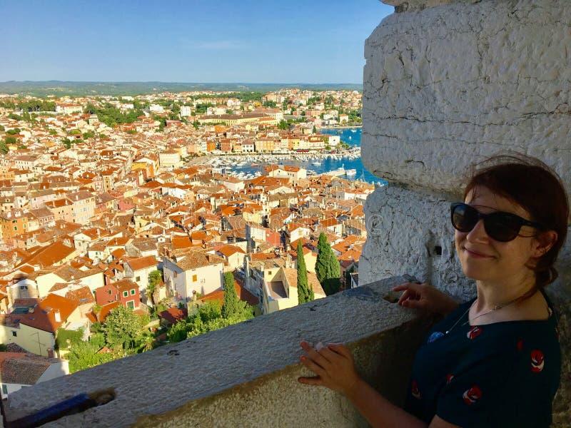 Молодая женщина самостоятельно стоя от вершины старой каменной колокольни смотря вне на красивом старом городке Rovinj, Хорватии стоковое фото