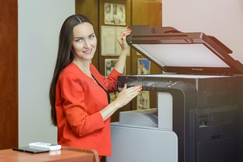 Молодая женщина секретарши делая фотокопии на офисе стоковые изображения