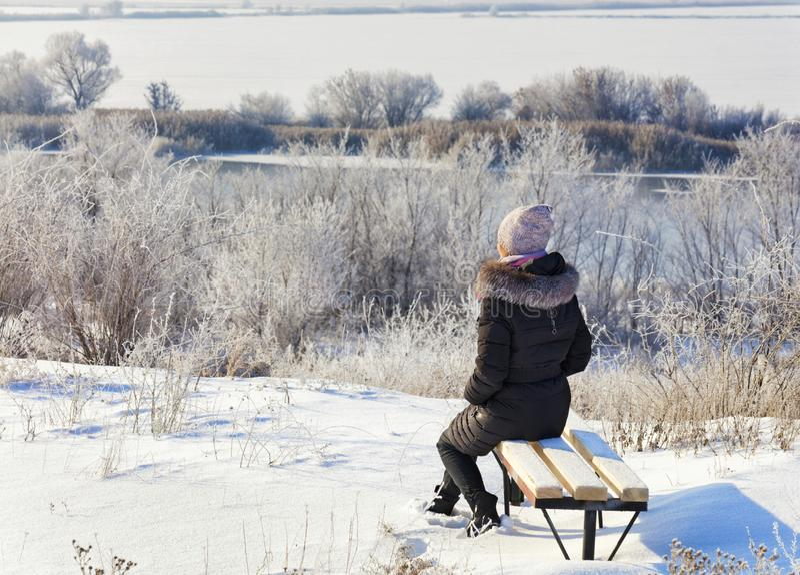 Молодая женщина сидит на деревянной скамье и взглядах на спокойном южном реке ошибки на солнечный зимний день стоковые фотографии rf