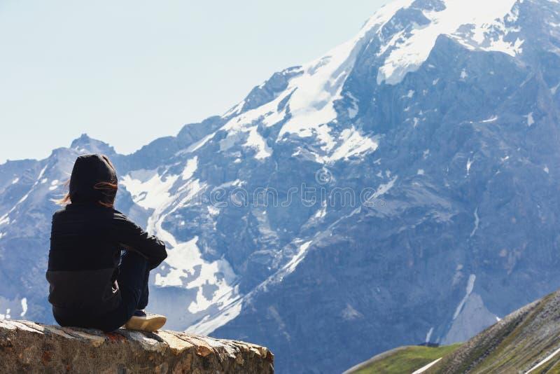 Молодая женщина сидит на утесе и взглядах на горах Взгляд от задней части человека смотря швейцарские Альп стоковые фотографии rf