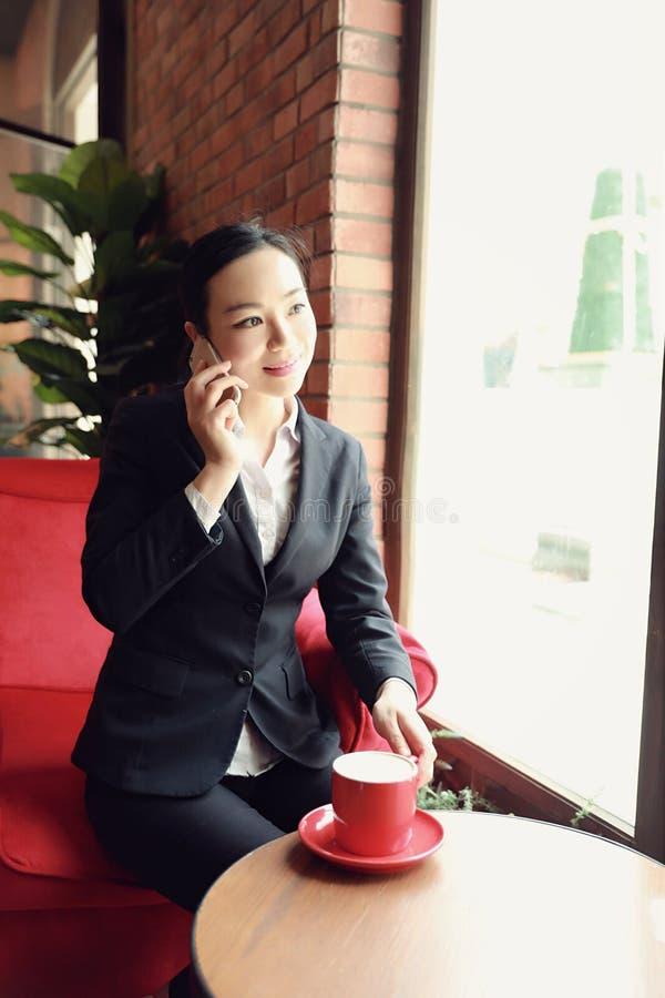 Молодая женщина сидя в кофейне на деревянном столе, выпивая кофе и используя smartphone стоковое изображение rf