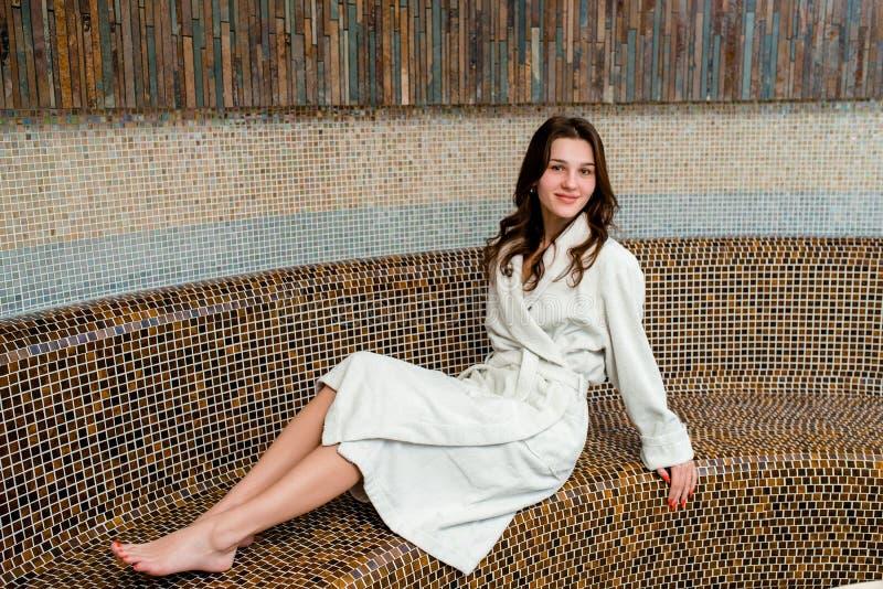 Молодая женщина сидя в сауне и усмехаться стоковые фото