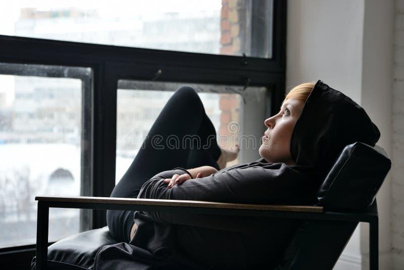 Молодая женщина сидя в стуле около окна стоковые изображения