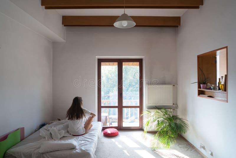 Молодая женщина сидя на кровати и смотря через окно стоковое изображение