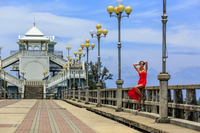 Молодая женщина сидя на мосте Sarasin стоковое фото
