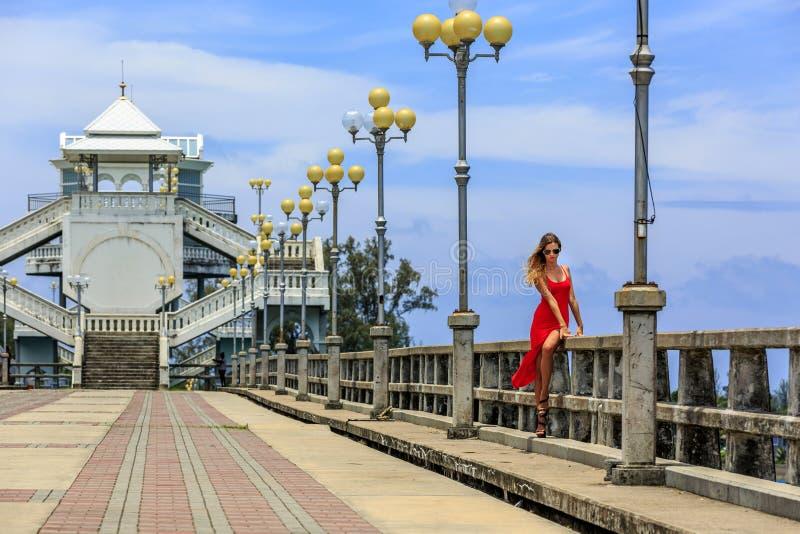 Молодая женщина сидя на мосте Sarasin стоковые изображения rf