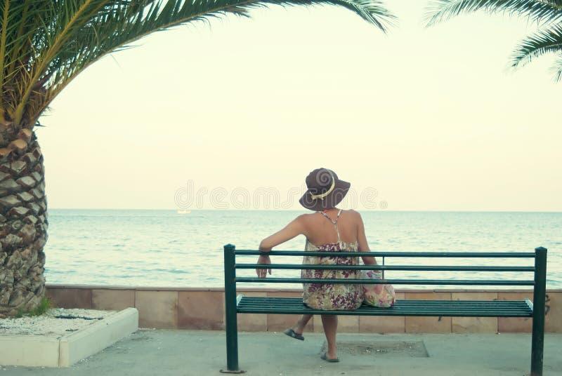 Молодая женщина сидя на стенде около моря стоковые изображения