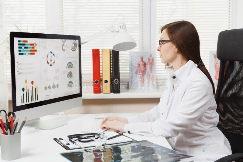 Молодая женщина сидя на столе, работая на современном компьютере с медицинскими документами в светлом офисе в больнице женщина стоковое изображение