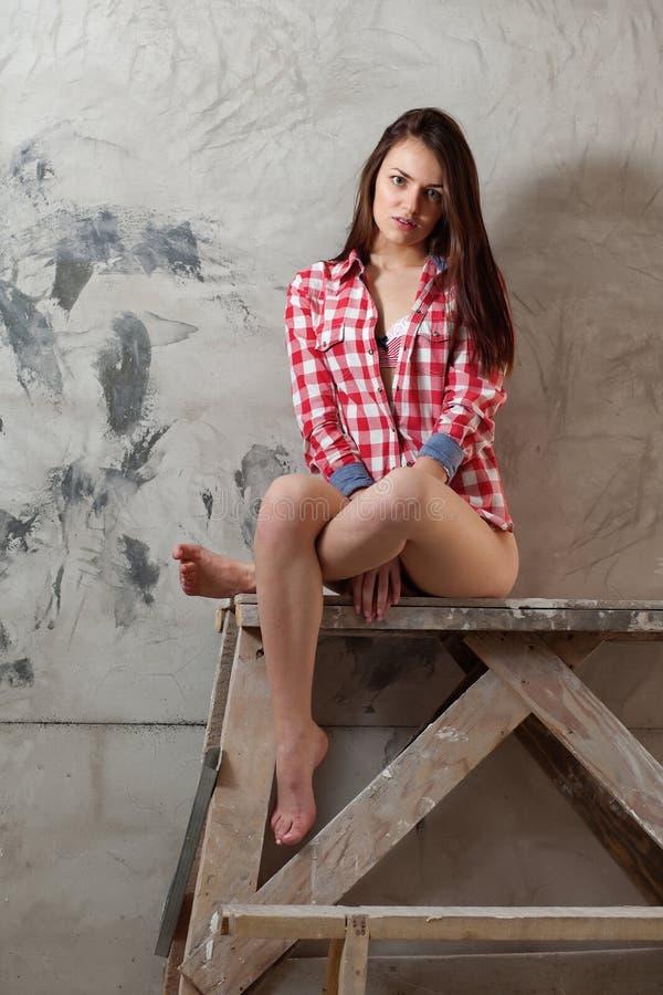 Молодая женщина сидя на таблице оформителя стоковое изображение rf