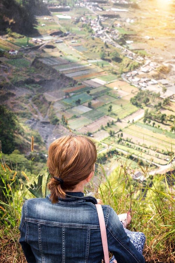Молодая женщина сидя на утесе с рюкзаком и смотря к горизонту Остров Бали Вулкан Batur стоковые изображения rf