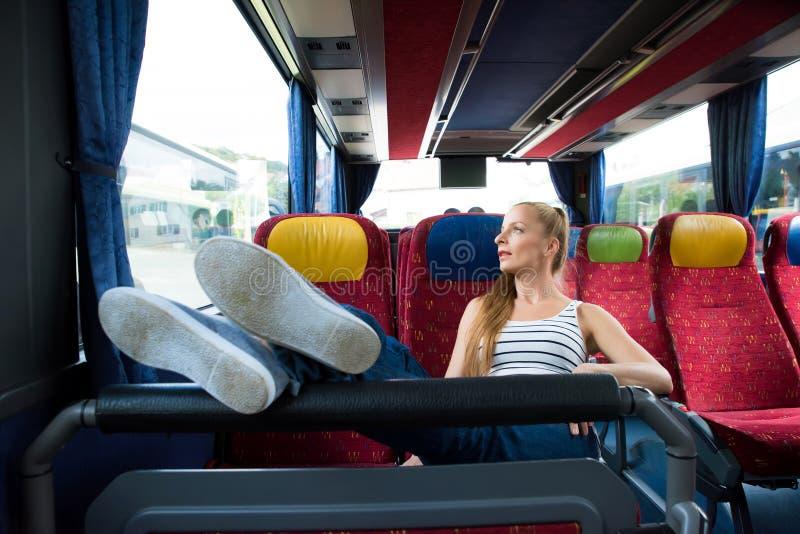 Молодая женщина сидя на шине стоковые фотографии rf