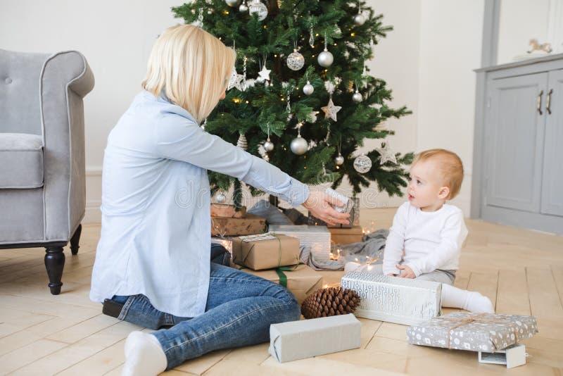 Молодая женщина сидя около рождественской елки с мальчиком стоковая фотография rf