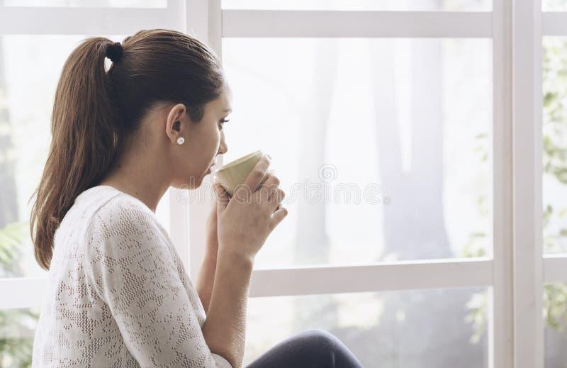 Молодая женщина сидя рядом с окном и смотря прочь стоковое фото