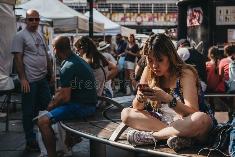 Молодая женщина сидя самостоятельно на стенде в рынке дороги Portobello, стоковое изображение rf