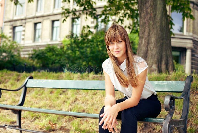 Молодая женщина сидя самостоятельно на стенде стоковое фото rf