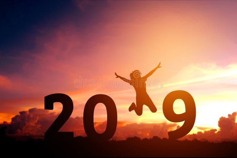 Молодая женщина силуэта скача до 2018 Новых Годов стоковые изображения