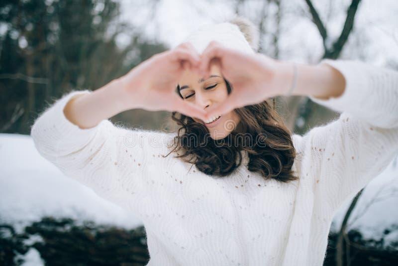 Молодая женщина сложила ее руки в форме сердца во время прогулки зимы стоковые изображения