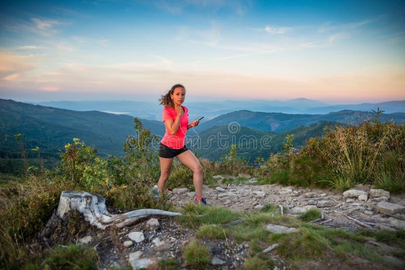 Молодая женщина слушая к музыке во время следа бежать в горах стоковое фото