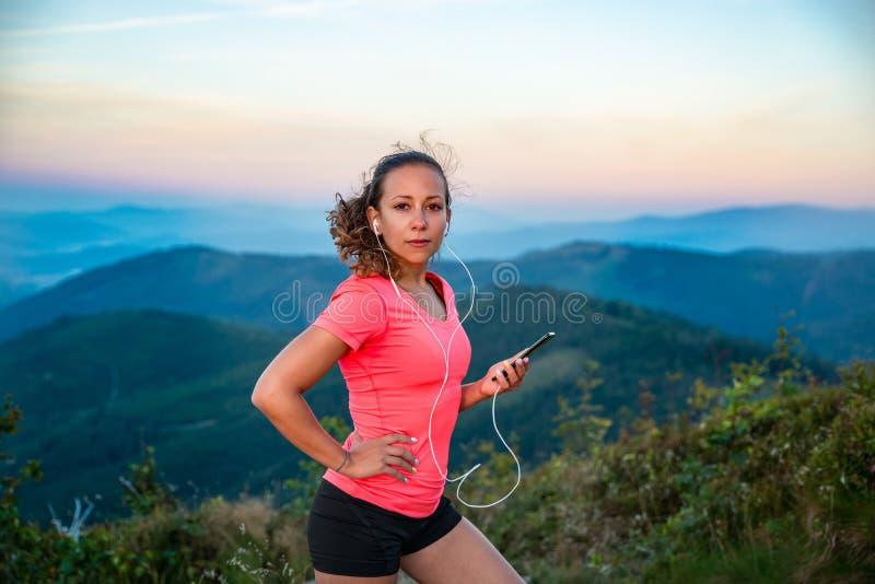 Молодая женщина слушая к музыке во время следа бежать в горах стоковое изображение rf