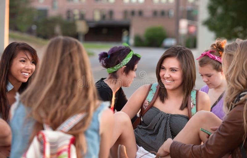 Молодая женщина смеясь над с друзьями стоковое фото rf