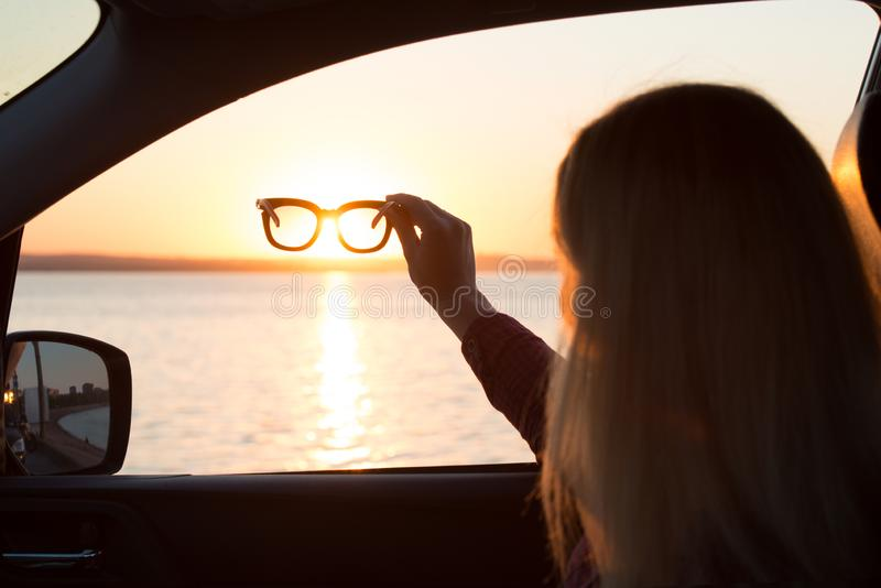 Молодая женщина смотрит вне окно автомобиля на заходе солнца на море, через солнечные очки стоковое изображение rf