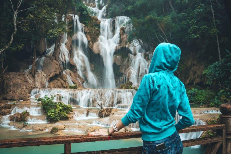 Молодая женщина смотрит и восхищает красивый водопад в диких джунглях Азии Белокурая девушка Backpacker или путешественника в син стоковое фото rf