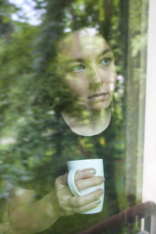 Молодая женщина смотря вне взгляд окна через стекло стоковые изображения rf