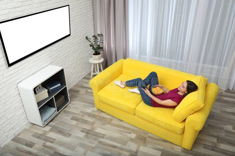Молодая женщина смотря ТВ и есть обломоки на софе дома, над взглядом стоковые фотографии rf