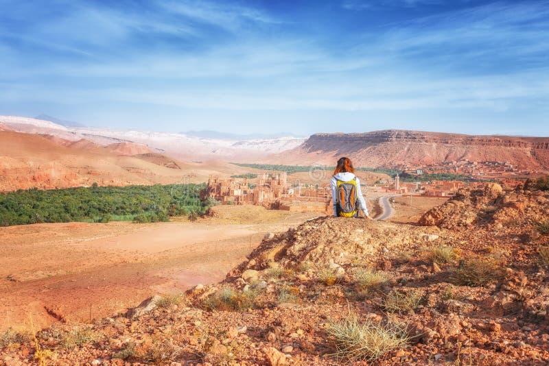 Молодая женщина смотря укрепленный город Glaoui Kasbah kasbah Telouet или ksar в марокканськом взгляде сверху Девушка путешествен стоковая фотография rf