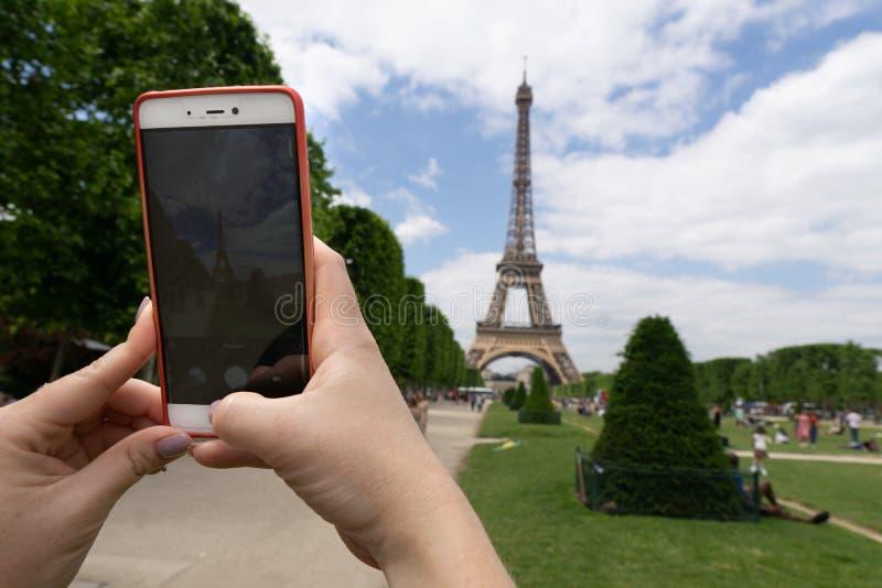 Молодая женщина снимает Эйфелеву башню на мобильном телефоне после обеда с голубым небом и белыми облаками стоковые фото